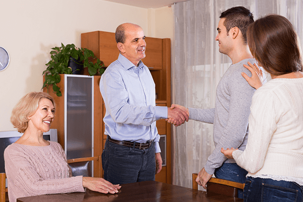 A boyfriend shaking the hand of his girlfriend's father as girlfriend and mother look on. (Photo: Shutterstock)