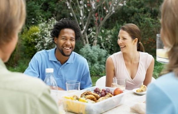 A black man and white woman having an outdoor dinner with her parents. (Photo: Fotosearch)