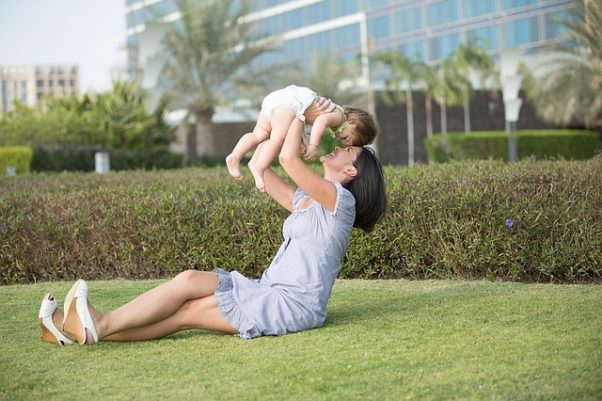 A mother sitting in the grass holding her baby daughter up over her head. (Photo: neildodhia/Pixabay)