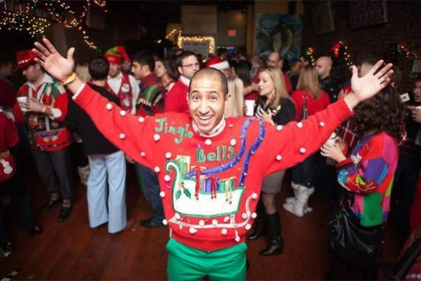 A bald man with outstretched arms wearing a red Crhistmas sweater and green pants in front of a group of holiday partiers. (Photo: Randy Moshen/Flickr)