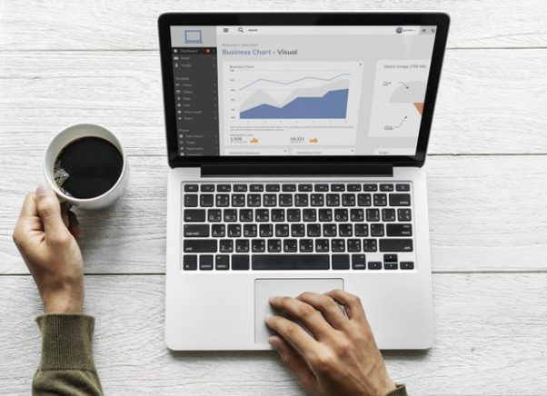 one hand on a lap top displaying a line graph on the rise while another hand holds a cup of coffee. (Photo: rawpixels/Pexels)