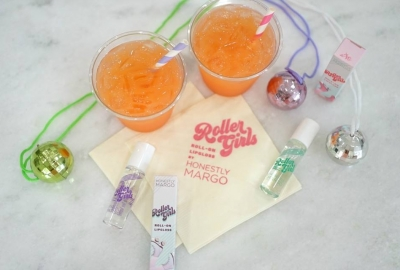Bottles of Roller Girls Roll-On Lip Gloss scattered on a table among christmas ornaments and two orange socas with straws. (Photo: Honestyl Margo/Facebook)