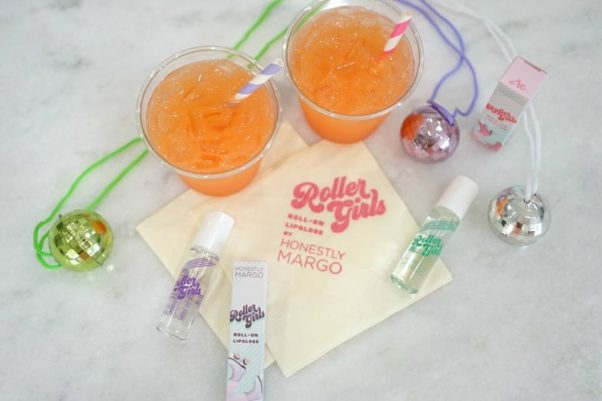Bottles of Roller Girls Roll-On Lip Gloss scattered on a table among christmas ornaments and two orange socas with straws. (Photo: Honestly Margo/Facebook)