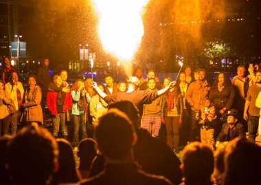 A man breathes a ball of fire into the air at Yards Park while surrounded by spectators. (Photo: Yards Park)