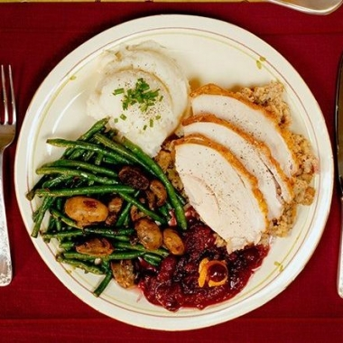 Plate of turkey cranberry sauce, green beans and mashed potatoes on a table with candles and saucer of gravy. (Photo: Getty Images)