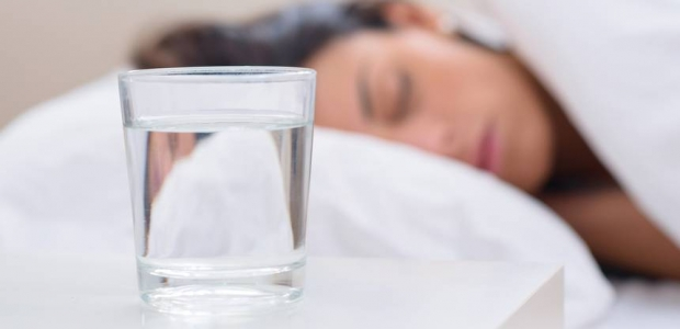 A woman sleeping in bed with a glass of water on the nightstand. (Photo: Shutterstock)