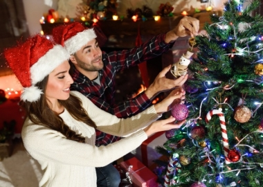 Man and woman wearing Santa hats decorating a Christmas tree. (Photo: Freepik)
