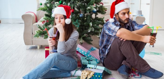 Unhappy woman and man sitting back-to-back infront of a Christmas tree wearing Santa hats and with cocktails. (Photo: Shutterstock)