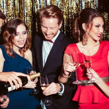 Two men and three women having a champagne toast at a New Year's Eve party. (Photo: Getty Images)