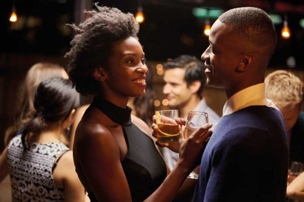 A black man and woman sharing a drink at a party. (Photo: Shutterstock)