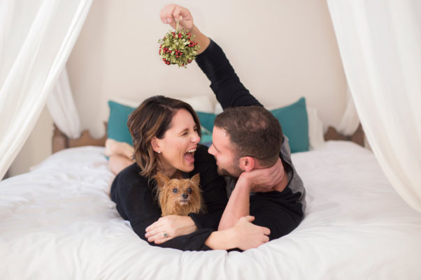 Man and woman lying in bed with man holding mistletoe. (Photo: Moments by T Photography)