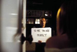 "Andrew Lincoln stands outside Keira Knightly's door holding a sign that says ""To Me You Are Perfect"" in ""Love, Actually."" (Photo: Universal Studios)"