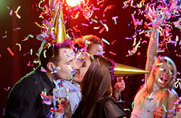 A man and womany at a New Year's Eve party earing gold party hats kissing as confetting rains down on them. (Photo: Getty Images)