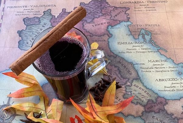 Vin brulee in a clear mug with a cinnamon stick sitting on top. The mug is on a map of Italy with fall leaves around it. (Photo: Lupo Verde Osteria)