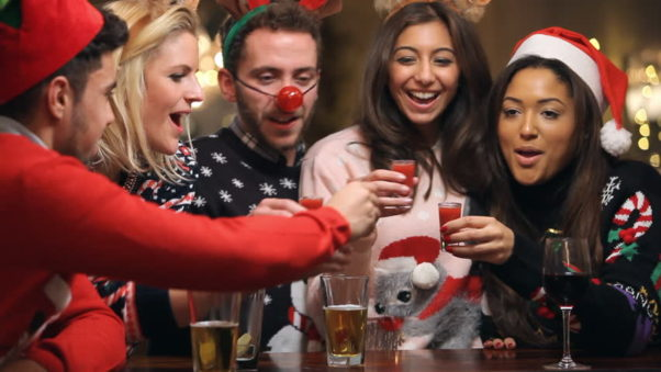 Friends in Christmas sweaters, reindeer antlers, a red nose, etc. having a toast. (Photo: Shutterstock)