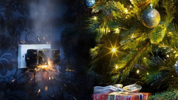 Christmas tree with gifts underneath beside an outlet with 2 things plugged in that are sparking. (Photo: iStock)