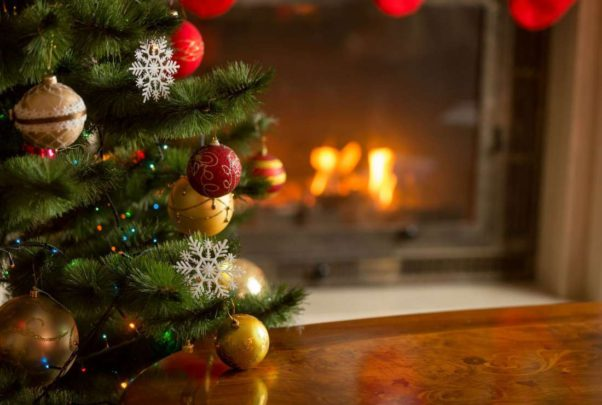 Christmas tree near a fireplace with a fire in it. (Photo: iStock)