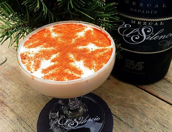 A holiday cocktail with a snowflake design on top in front of pine and a bottle of El Silencio mezcal. (Photo: El Silencio)