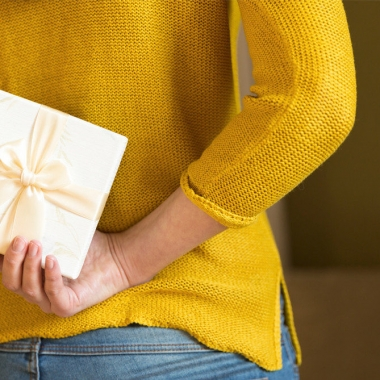 woman in yellow sweater in jeans hodling an envelope with a gift certificate in it behind her back. (Photo: Getty Images)