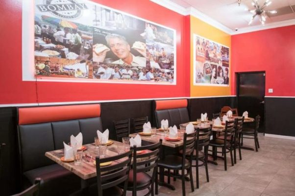 The inside of Bombay Street Food with red and yellow walls with photos depicting scenes from Bombay with Anthony Bourdain in the middle. (Photo: Bombay Street Food)