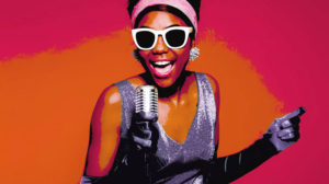 A black woman wearing sunglasses and a pink head band in a silver dress sings into a microphone. (Photo: Signture Theatre)