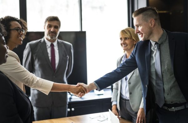 Men and women in an office dressed in suits shaking hands. (Photo: Rawpixel/Pexels)