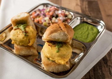 Two vada pavs on a metal tray with cilantro-ginger chutney and sauce. (Photo; Bombay Street Food)