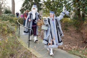 Grandfather Frost and the Snow Maiden dressed in gray and black walk down a path at Hillwood Estate. (Photo: Hillwood Estate)
