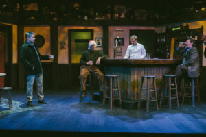 Three men in a pub, one wearing a Santa hat, with a bartender behind the bar. (Photo: Keegan Theatre)