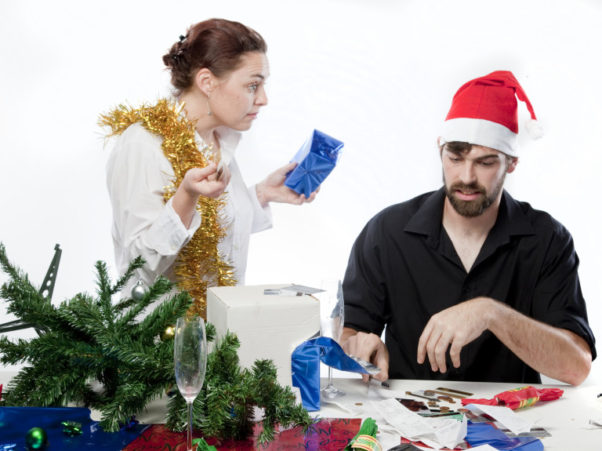 woman with gold garland on her and man wearing Santa cap sitting at a table argue while wrapping presents. (Photo: Shutterstock)