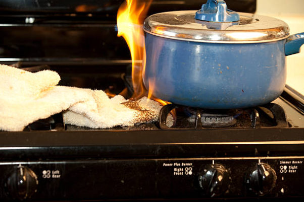 Blue dutch oven on gas stovetop with towel beside it that has caught on fire. (Photo: iStock)