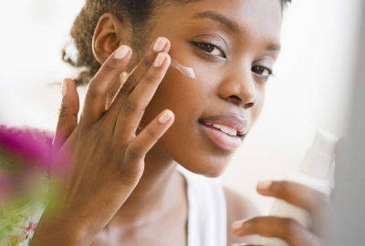 A black woman putting sunblock on her face. (Photo: Getty Images)