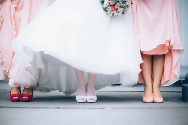 A bride with bridesmaids on both sides of her all holding up their dresses show you can see their shoes. (Photo: StarFlames/Pixabay)