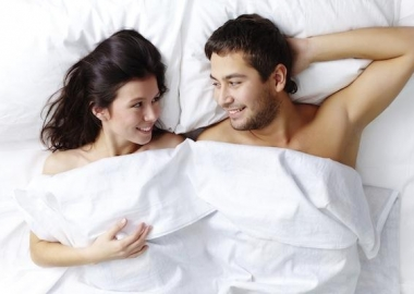 Man and woman in bed under the sheets staring at each other. (Photo: Shutterstock)