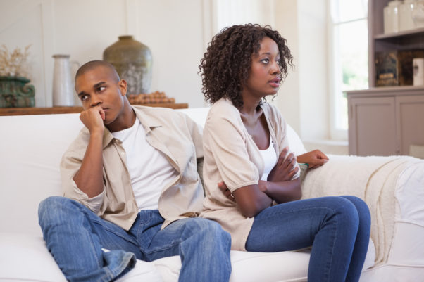 Black couple arguing on a couch. (Photo: Shutterstock)