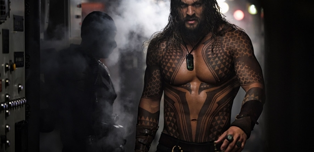 Actor Jason Momoa as a tattooed and shirtless Aquaman walks past another man in a submarine. (Photo: Warner Bros. Pictures)
