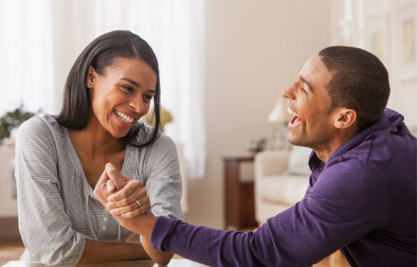 Black man and woman arm wrestling in living room. (Photo: Getty Images)