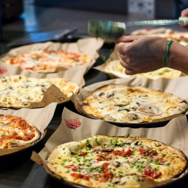 An employee sprinkles pesto on top of a cooked pizza with 5 other cooked pizzas on the counter. (Photo: MOD PIzza)
