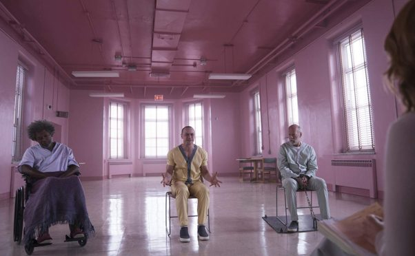 Morgan Freeman, James McAvoy and Bruce Willis sit chained in their chairs in a mental hospital. (Photo: Universal Pictures)