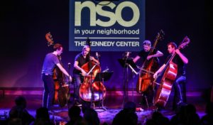 "A quartet of NSO cellists play on a stage in front of an ""NSO in Your Neighborhood"" sign. (Photo: Kennedy Center)"