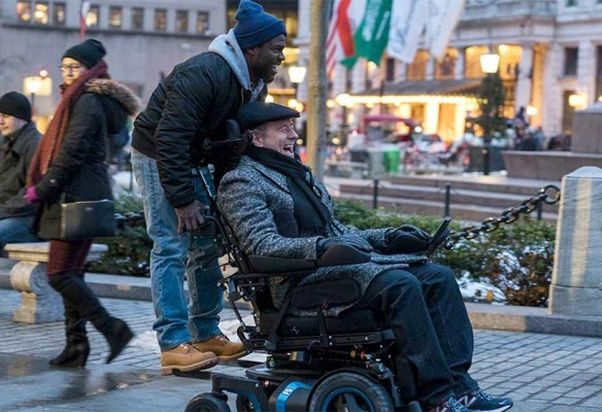 Kevin Hart standing on the back of a wheelchir driven by Bryan Cranston in The Upside. (Photo: The Weinstein Co.)