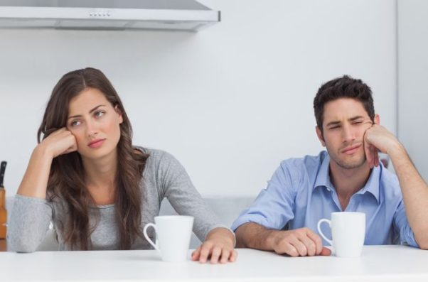 Couple sitting in the kitchen with coffee mugs staring in opposite directions. (Photo: Shutterstock)