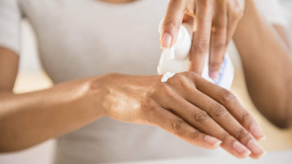 African American woman putting lotion on her hand. (Photo: Getty Images)