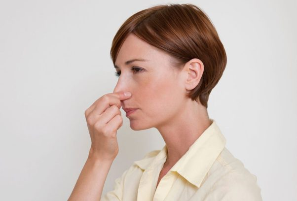 A woman pinching her nose while holding her breath. (Photo: Masterfile)
