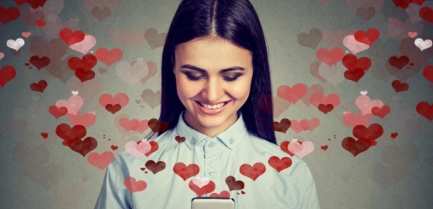 Happy woman sending love texts with red and pink hearts coming out of her cell phone. (Photo: Shutterstock)