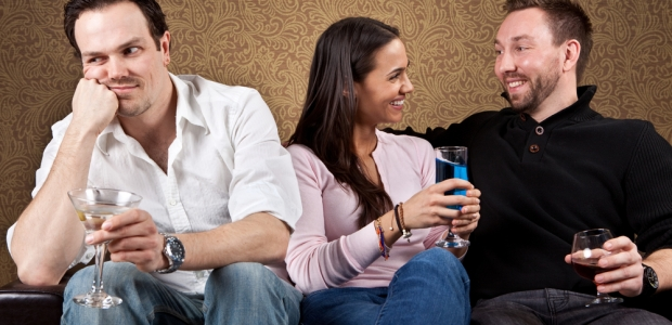 Three people sitting on a couch. Single man on left looks bored while woman and man have a fun conversation. (Photo: Shutterstock)