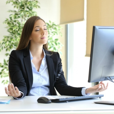 Hispanic woman meditating at her office desk. (Photo: Alamy)