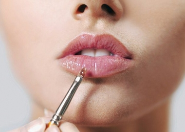 Woman applying lip paint to her full lips. (Photo: Getty Images)