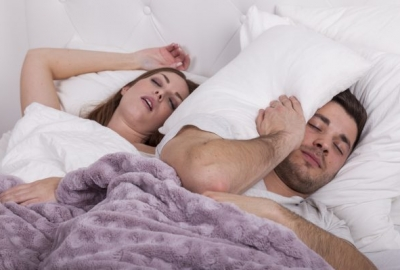 A couple in bed. The woman is snoring and the man has a pillow wrapped around his head. (Photo: iStock)