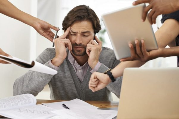 Man understress at desk with coworkers handing him a cell phone, notes, a computer tablet and pointing to a watch from different directions. (Photo: iStock)